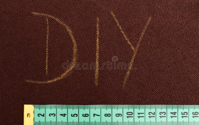 Le texte de DIY sur le tissu brun a souligné photos stock