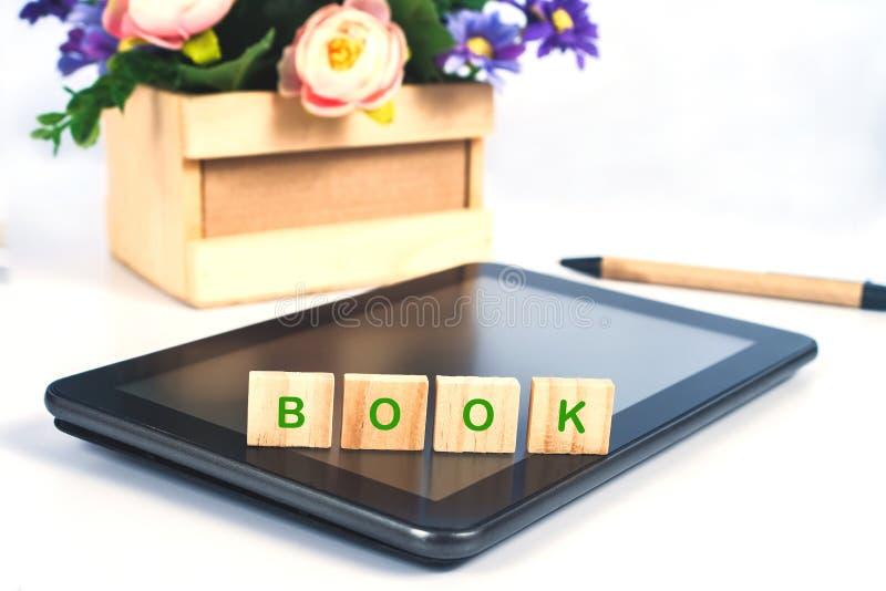 Le texte de livre sur le bloc en bois se connectent le comprimé mobile pour des achats en ligne image libre de droits