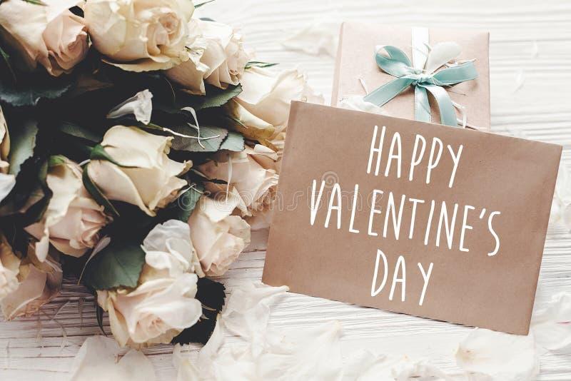 Le texte heureux de Saint-Valentin se connectent la carte de voeux de métier et les roses blanches, boîte-cadeau sur le fond en b images stock
