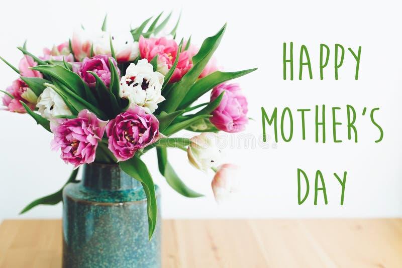 Le texte heureux du jour de mère se connectent le beau double bouquet de tulipes de pivoine dans le vase dans la lumière Carte de images stock
