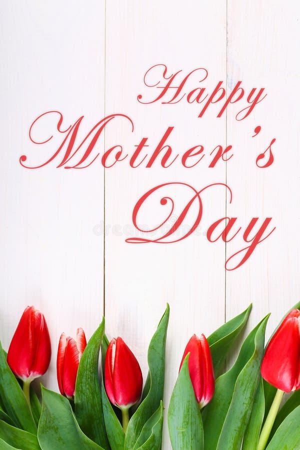 le texte heureux du jour de mère se connectent les tulipes roses sur le fond en bois rustique blanc Concept de carte de voeux ima images stock