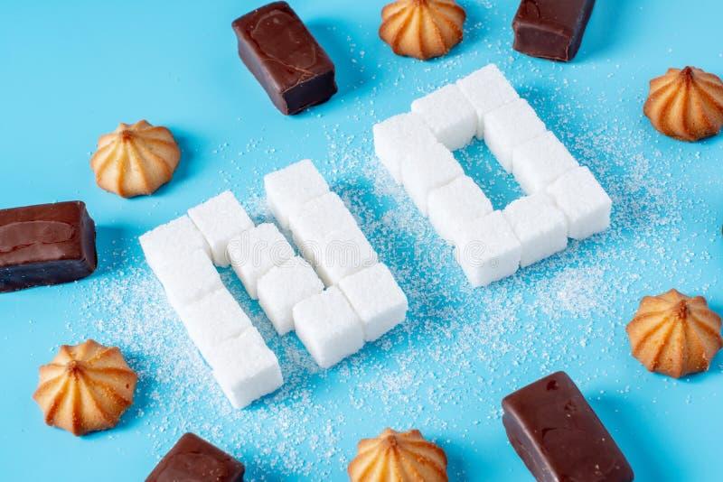 Le texte non n'est garni des cubes en sucre avec des bonbons et des biscuits Mal à la santé du bonbon et au rejet du sucrose photos libres de droits