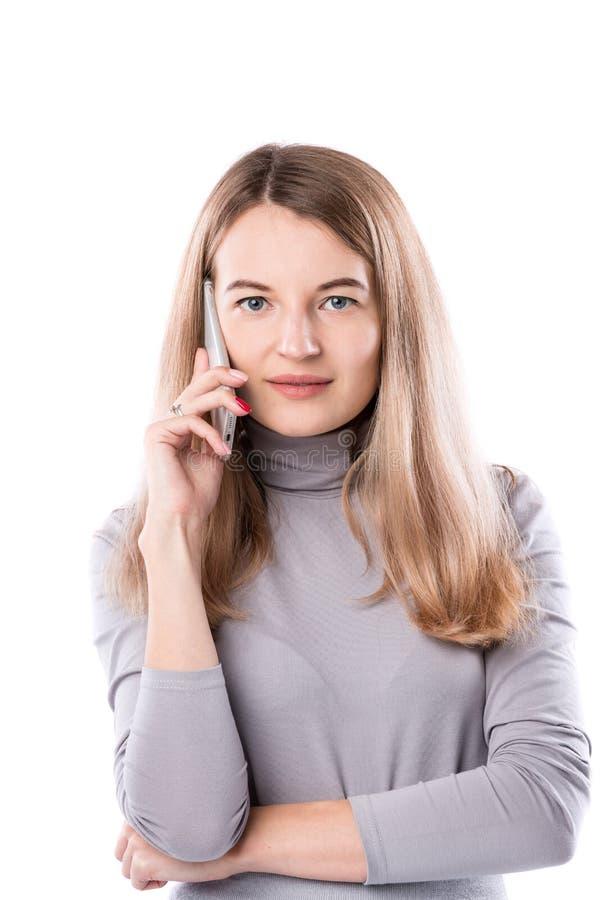 Le thème d'une femme d'affaires et des conversations téléphoniques La belle jeune femme caucasienne utilise un combiné de smartph image stock