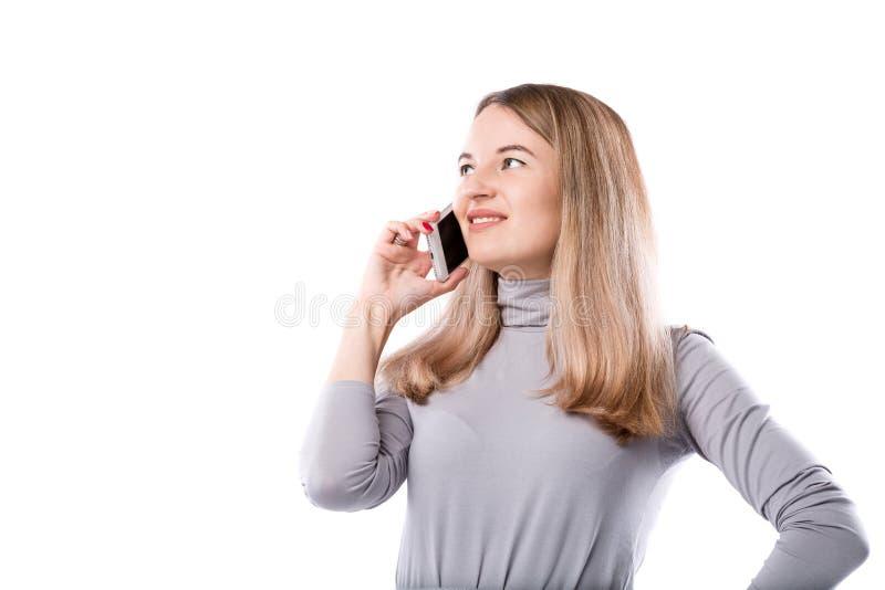 Le thème d'une femme d'affaires et des conversations téléphoniques La belle jeune femme caucasienne utilise un combiné de smartph photographie stock