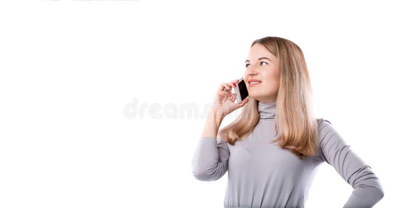 Le thème d'une femme d'affaires et des conversations téléphoniques La belle jeune femme caucasienne utilise un combiné de smartph images libres de droits