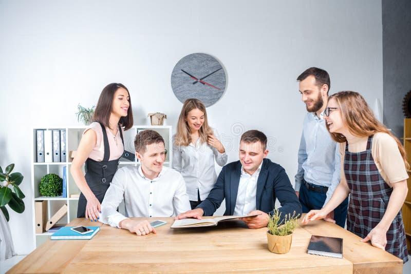 Le thème est des affaires et travail d'équipe Un groupe de jeunes employés de bureau caucasiens de personnes tenant une réunion,  photo libre de droits