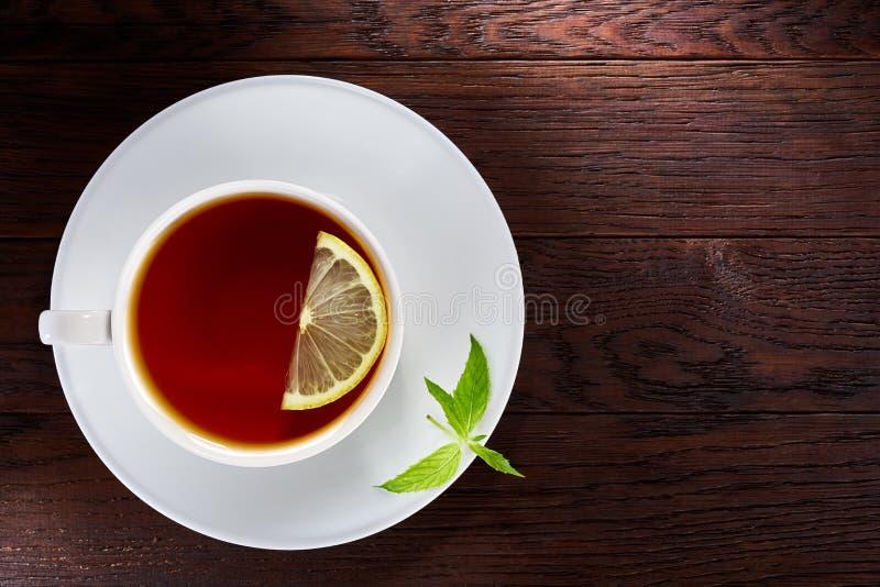 Le thé avec le citron dans la tasse blanche, bâtons de cannelle, a tricoté l'écharpe de laine sur la table en bois image stock