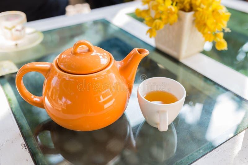 Le thé chaud s'est renversé dans la tasse avec le pot orange photographie stock