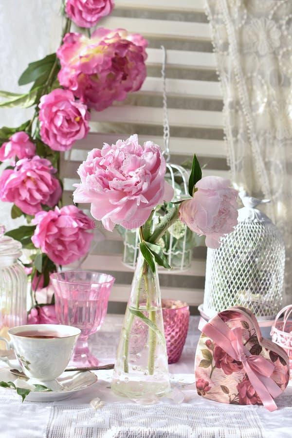Le thé de fruit dans la belles tasse et pivoine de porcelaine fleurit photo stock