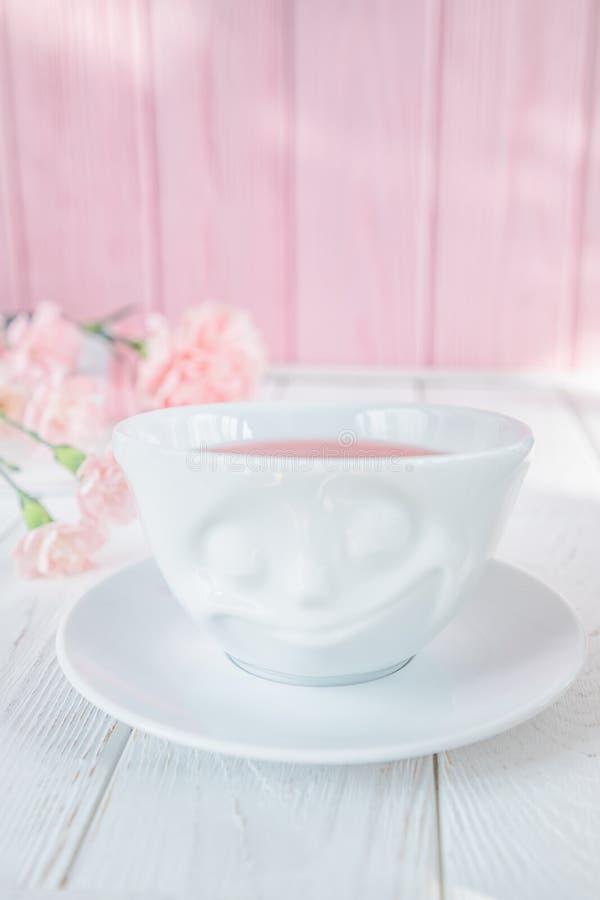 Le thé de fruit dans la tasse blanche et l'oeillet rose fleurit sur un fond blanc L'espace libre photo stock