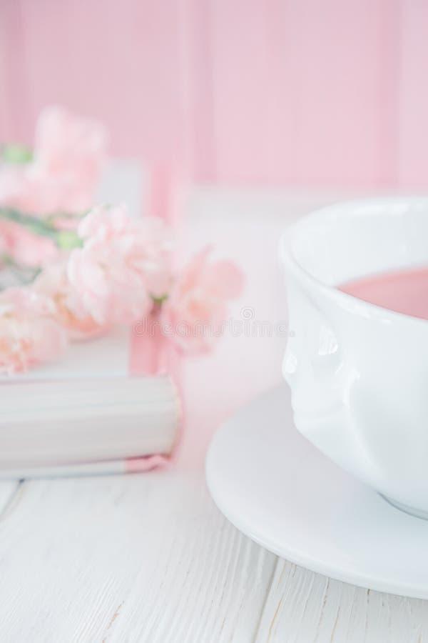 Le thé de fruit dans la tasse blanche, le livre et l'oeillet rose fleurit sur un fond blanc L'espace libre photo stock