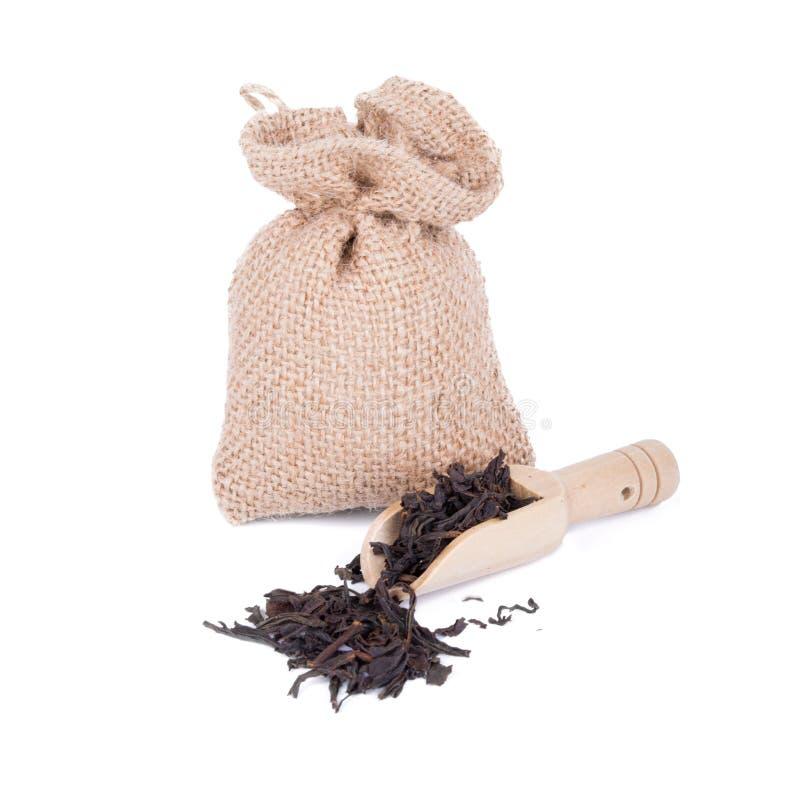 Le thé noir sec part dans le sac en bois de scoop et de sac avec le thé d'isolement sur le fond blanc images libres de droits
