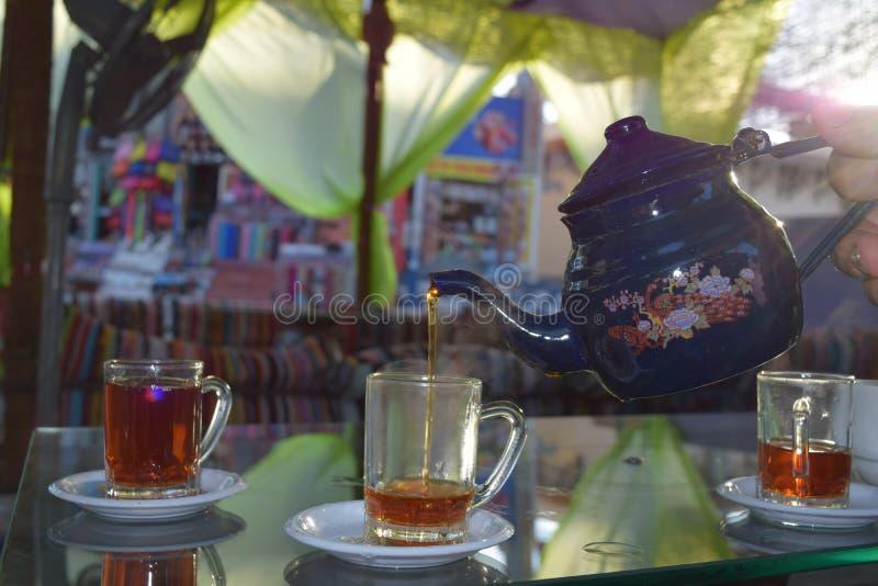 Le thé traditionnel s'est renversé des tasses d'une théière en café arabe photo stock