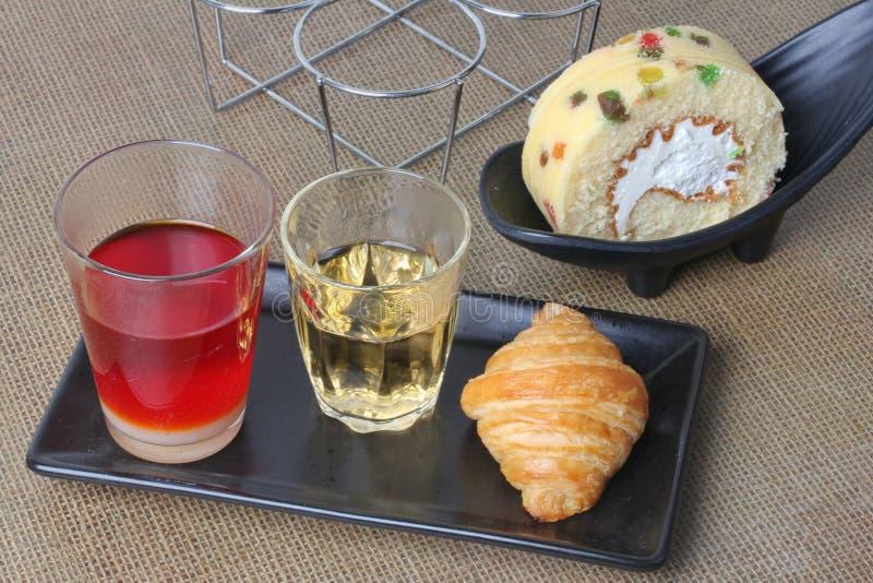 Le thé traditionnel thaïlandais de lait a servi avec le gâteau de fruit de thé, de croissant et de petit pain photos stock