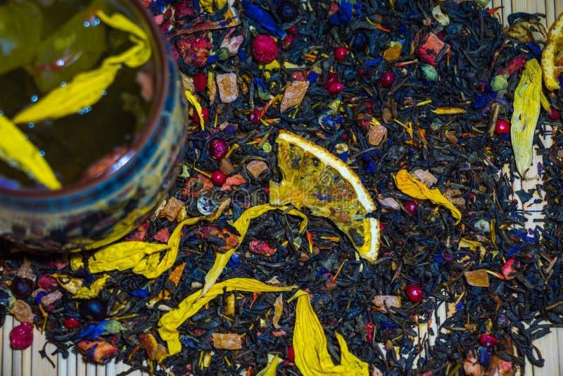 Le thé vert parfumé avec les pétales jaunes de fleur est brassé dans une tasse avec les ornements chinois de culture image libre de droits