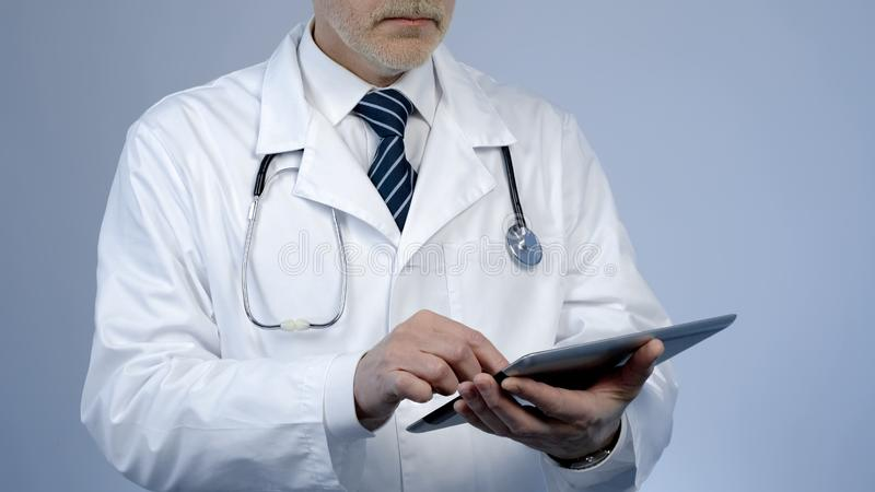 Le thérapeute à l'aide de la tablette pour vérifier le disque médical de patients ou l'essai en laboratoire résulte images libres de droits