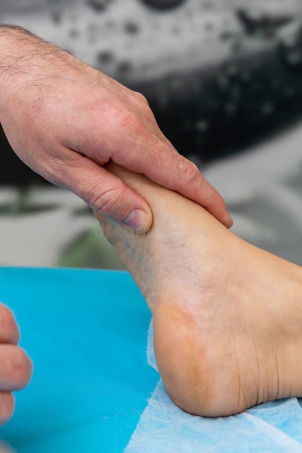 Le thérapeute d'ostéopathe fait la manipulation et le massage au pied le patient image stock