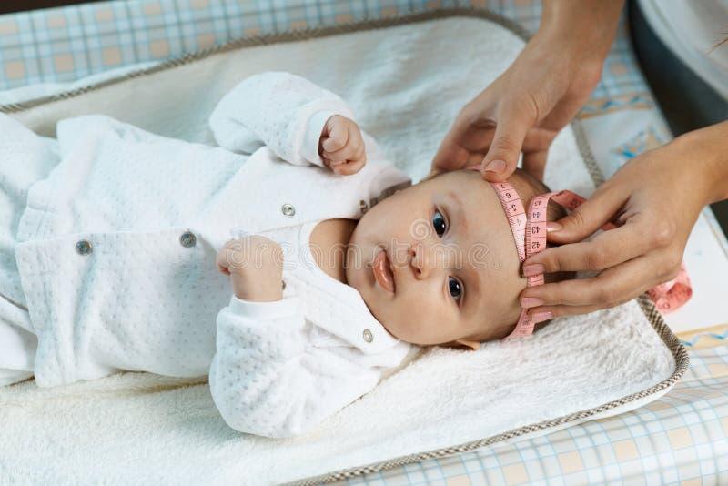 Le thérapeute mesure la tête de taille du beau bébé images stock