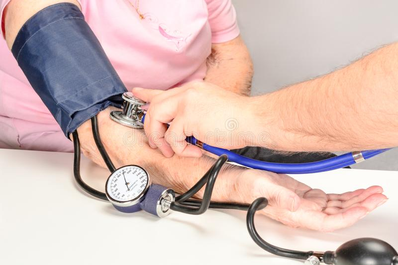 Le thérapeute mesure la tension artérielle d'une femme agée avec un tonometer classique photographie stock libre de droits