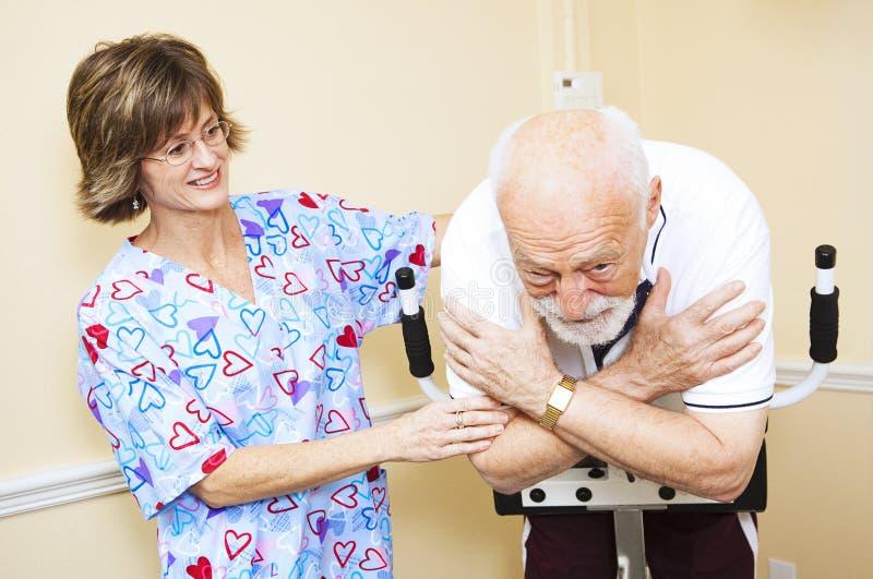 Le thérapeute physique travaille avec l'aîné image libre de droits