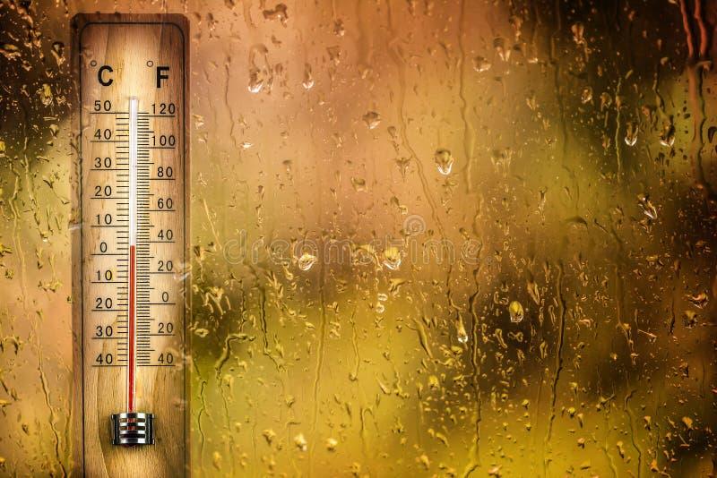 Le thermomètre derrière la fenêtre de baisses montre une basse température photos libres de droits