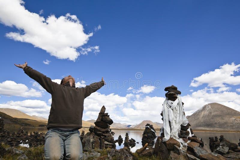 Le Thibet : homme priant avec les bras ouverts photo stock