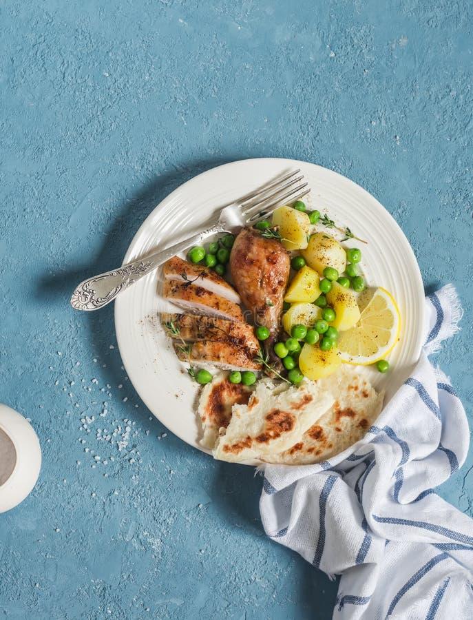 Le thym de citron a fait le poulet, les pommes de terre et les pois cuire au four d'un plat blanc sur un fond bleu photo libre de droits