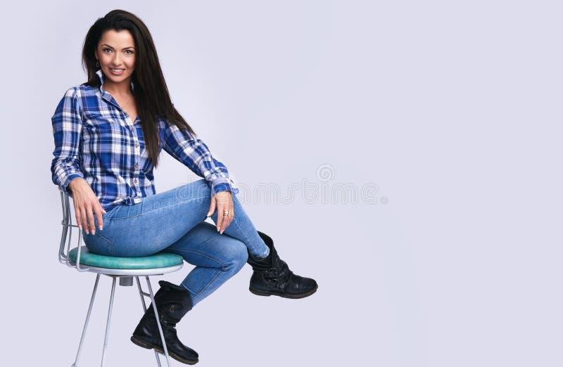 Le tillfälligt kvinnasammanträde på en stol isolerat arkivbilder