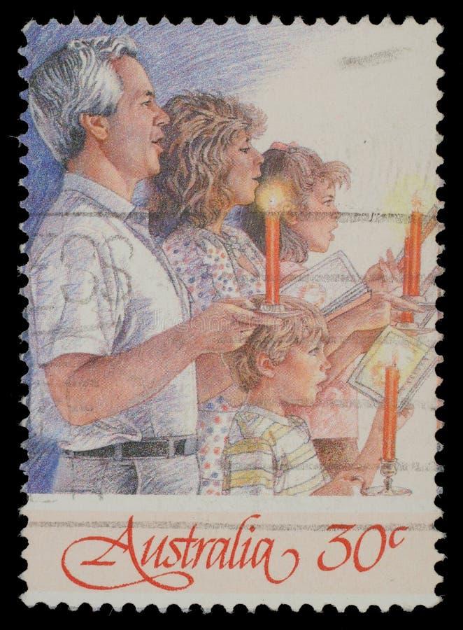 Le timbre de Noël imprimé dans l'Australie montre la famille chantant avec des bougies photo libre de droits
