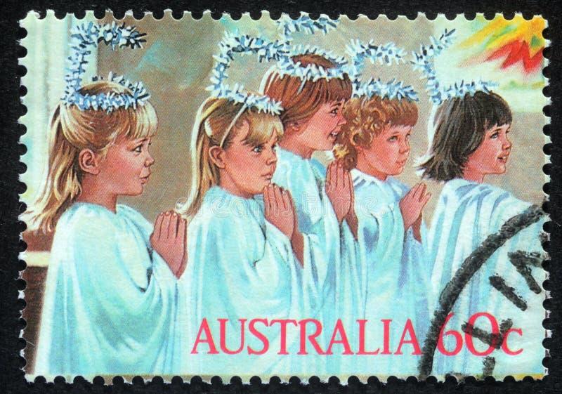 Le timbre de Noël imprimé dans l'Australie montre le jeu d'enfants à la famille sainte photo libre de droits
