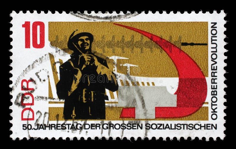 Le timbre imprimé en RDA montre le cinquantième anniversaire de la révolution russe d'octobre images libres de droits