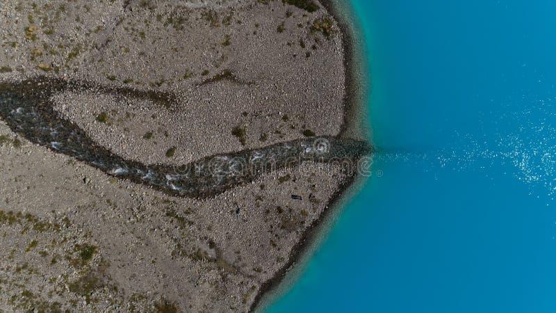 Le tir aérien du lac glaciaire bleu Blavatnet et de la rivière vide dans lui, Alpes de Lyngen image libre de droits