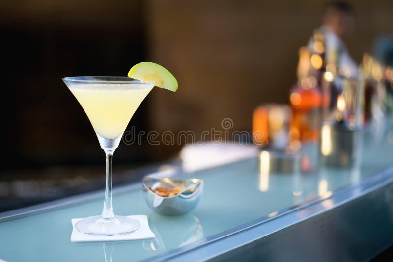 Le tir alcoolique de martini de pomme de cocktail à la barre avec la tache floue de barten images stock