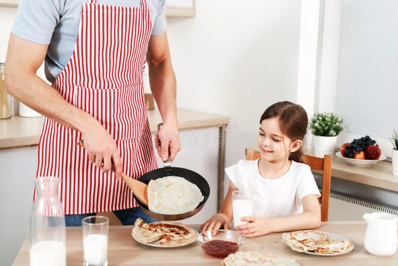Le tir cultivé de l'homme dans le tablier impliqué dans la cuisson, crêpes délicieuses de fritures pour sa fille, preapres déjeun image libre de droits