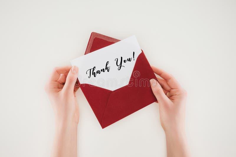 le tir cultivé de la femme ouvrant l'enveloppe rouge avec vous remercient lettrage sur le papier photographie stock libre de droits