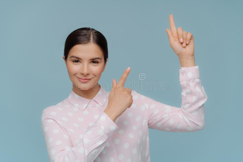 Le tir d'intérieur de beaux points de dame de brune vers le haut avec les deux doigts antérieurs, a l'expression heureuse, utilis image stock