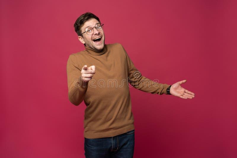Le tir d'intérieur de l'homme gai dans les lunettes et des vêtements sport indique heureusement à vous, choisit de concurrencer,  images libres de droits