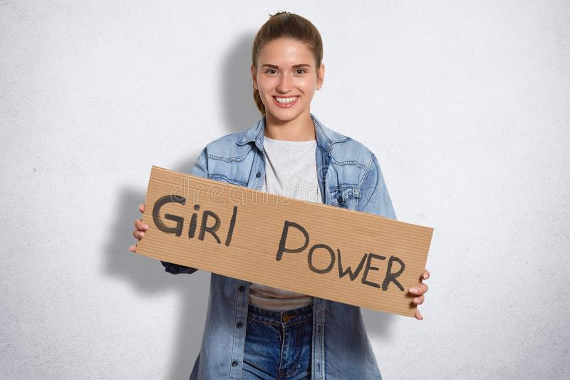 Le tir d'intérieur de la belle femme appartient au mouvement du féminisme, a l'expression gaie, tient le plat avec la puissance d photos libres de droits