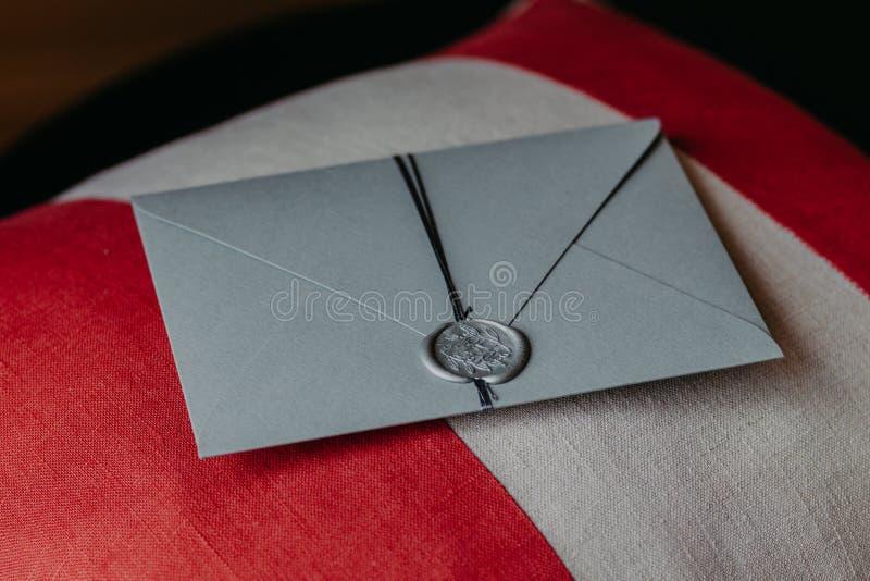 Le tir d'intérieur de la carte de papier grise élégante d'invitation se trouve sur l'oreiller de sofa Invitation pour l'anniversa photo libre de droits