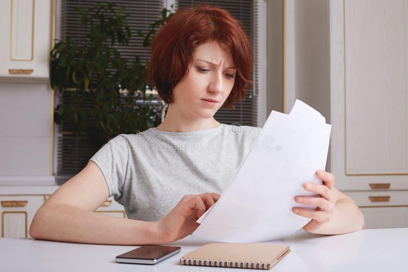 Le tir d'intérieur de la femme d'affaires réussie a l'expression sérieuse, étudie des documents à la maison, habillé en passant,  image stock