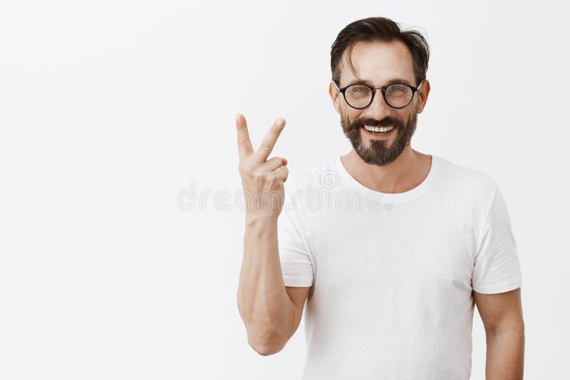 Le tir d'intérieur du bel homme sûr et heureux avec les verres à la mode montrant le numéro deux ou lèvent le vôtre geste, souria image libre de droits
