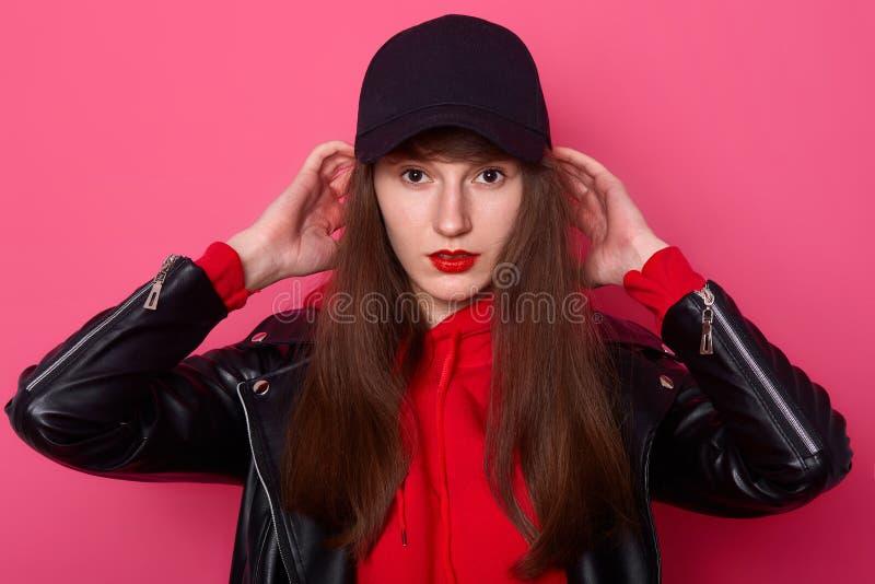Le tir d'intérieur du jeune adolescent utilisant le hoodie rouge élégant, la veste en cuir et le chapeau noir, garde des mains su image stock