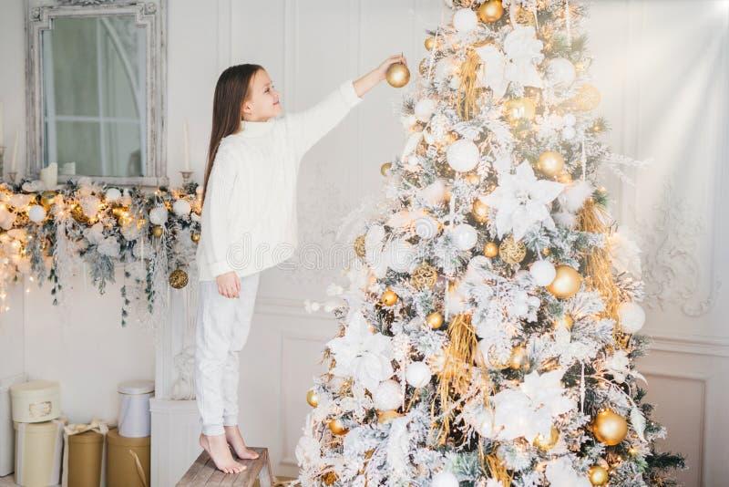 Le tir d'intérieur du petit enfant dans des vêtements blancs, décore l'arbre de nouvelle année, se tient sur la pointe des pieds, image stock