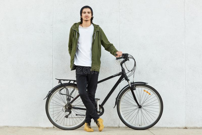 Le tir d'isolement de l'adolescent masculin de hippie élégant s'est habillé dans l'équipement élégant et les espadrilles, tient l photos libres de droits