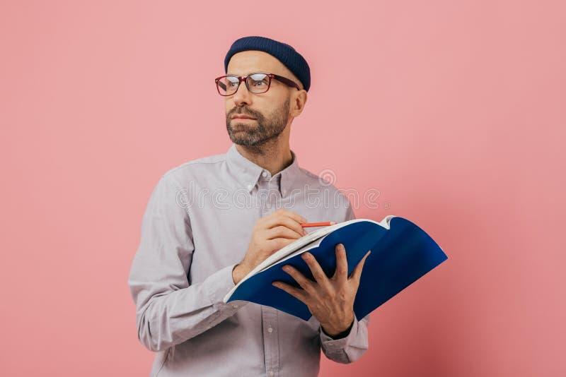 Le tir de l'homme non rasé songeur concentré de côté, pense à quoi écrire L'architecte masculin bel tient le livre et le crayon, images stock