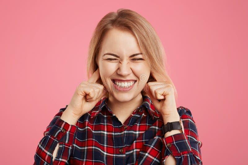 Le tir de studio de la jolie femme serre des dents et des oreilles de prises avec mécontentement comme entend bruit désagréable o image stock