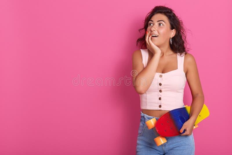 Le tir demi-longueur de la femme bouclée étonnée heureuse, passant le temps avec des amis, préparent pour la planche à roulettes  images stock