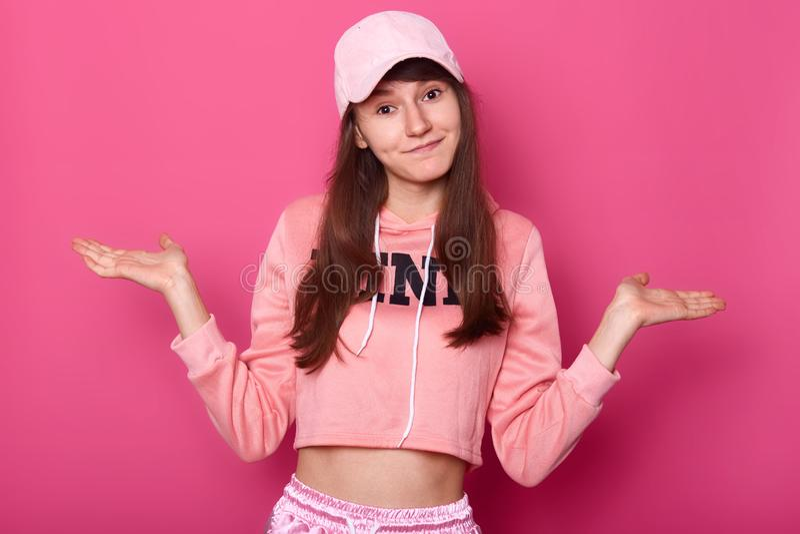 le tir du joli adolescent de brune attrayante, utilise le hoodie rose et le chapeau, regardant la caméra, a de longs cheveux fonc photos stock
