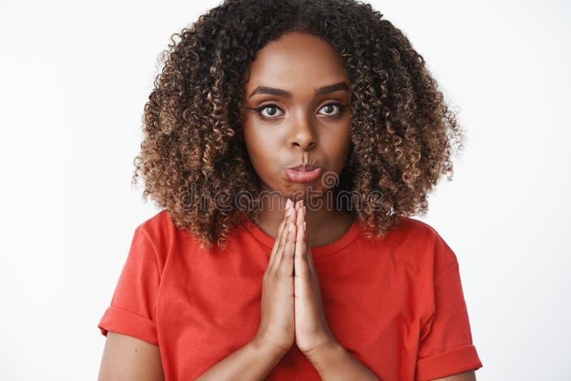 Le tir en gros plan de la fille boudante tenant des mains dans prient et regardant plein d'espoir la cam?ra en tant que prier pou images libres de droits