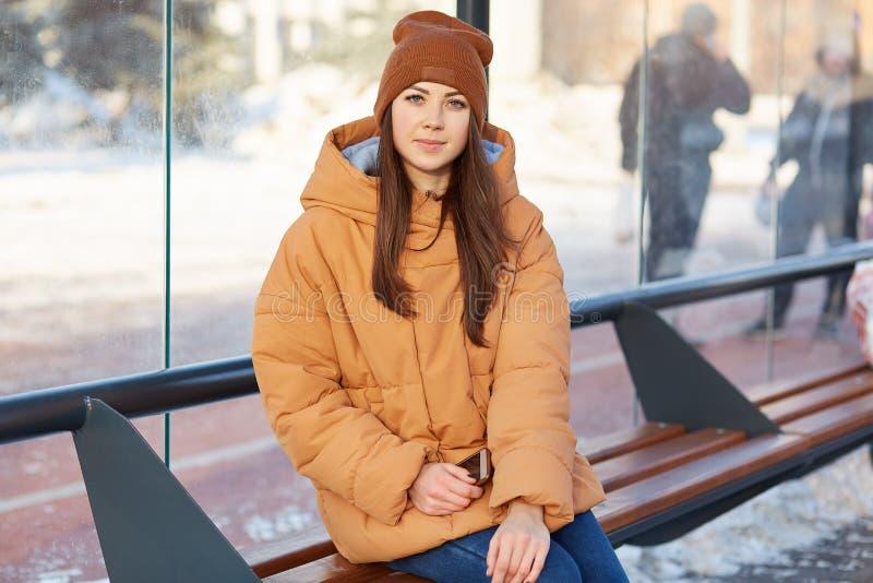 Le tir extérieur de la brune agréable à regarder, habillé dans le chapeau et la veste bruns, se repose à la gare routière, tient  photo libre de droits